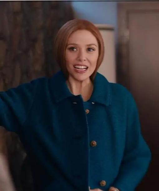 Elizabeth Olsen wearing a blue wool coat in the WandaVision TV series