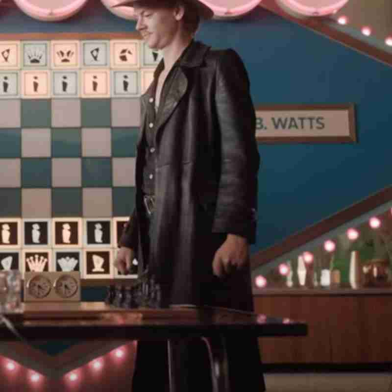Thomas Brodie-Sangster as Benny Watts wearing a matte black longcoat in The Queen's Gambit
